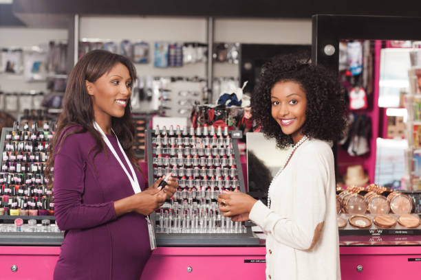 customer with a beauty consultant. - makeup for pregnant women stock photos and pictures
