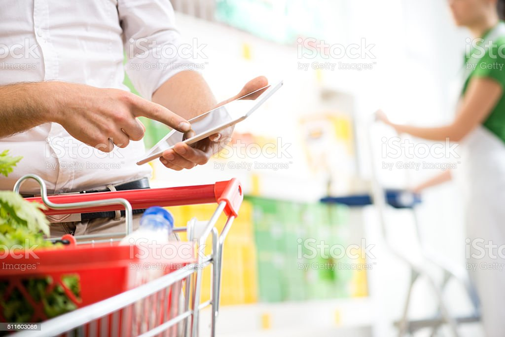 Customer with tablet at supermarket stock photo