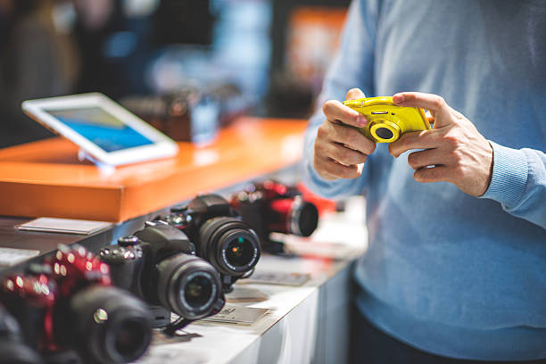 customer with yellow camera - sale lenses stock photos and pictures