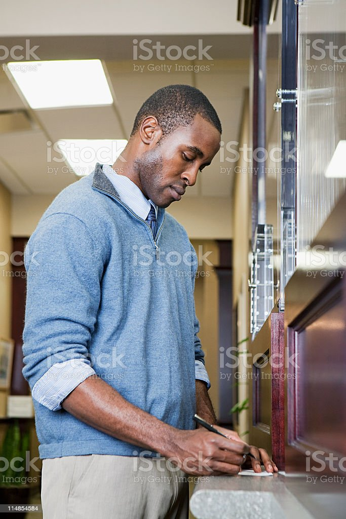 Customer writing cheque at bank counter stock photo