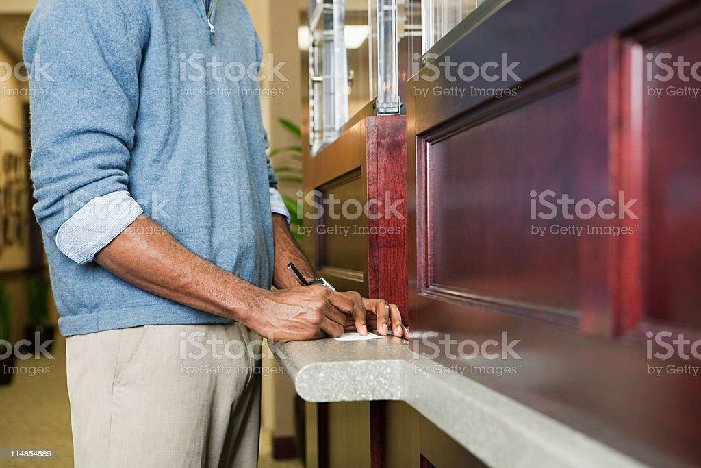 Kunde einen Scheck bei der bank counter – Foto