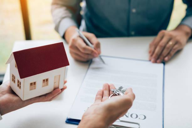 Kunden schreiben Unterzeichnung Unterzeichnung auf Papier Vertrag mit Immobilienmakler und geben Schlüssel an den Kunden. – Foto