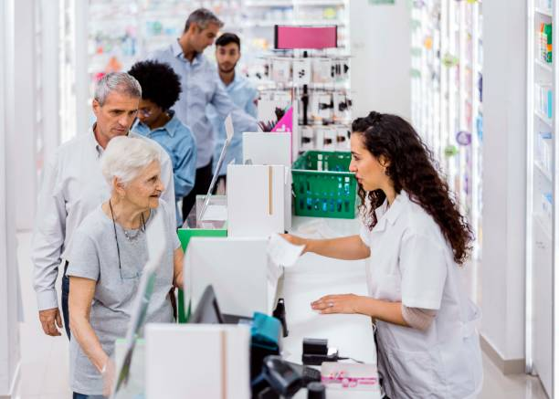 Customers and chemist in drugstore stock photo