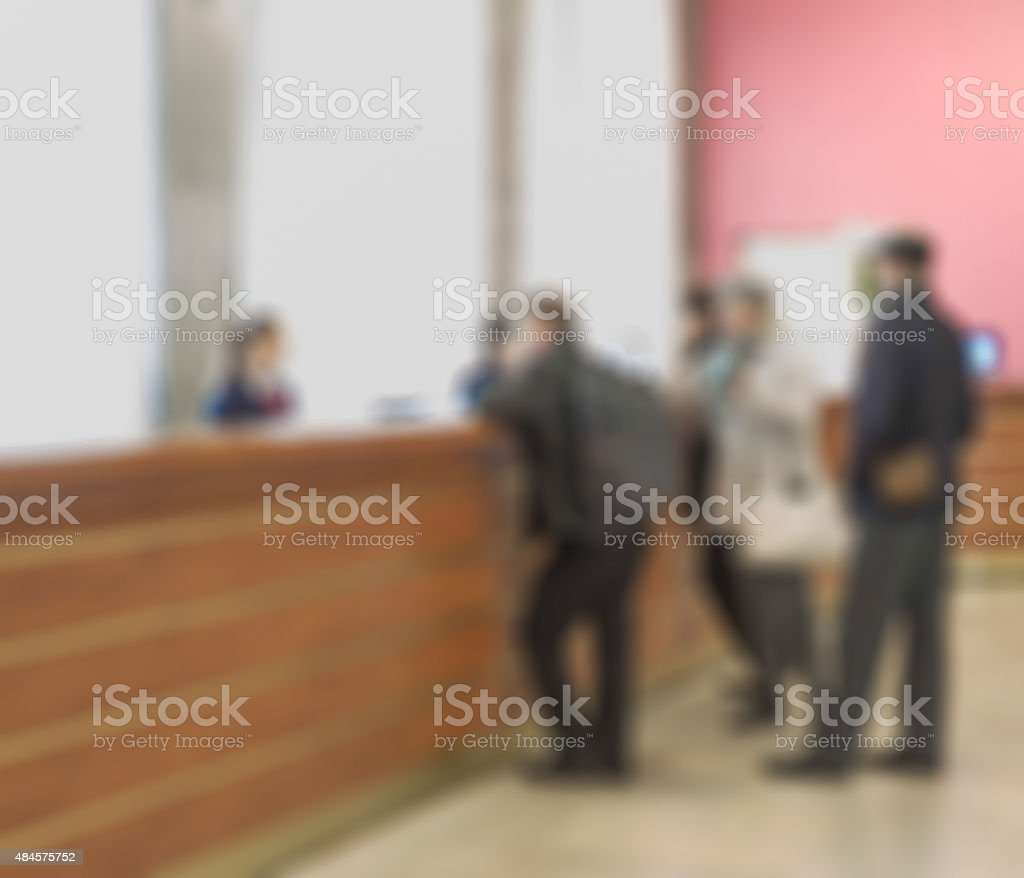 Customers and receptionist at counter in blur motion stock photo