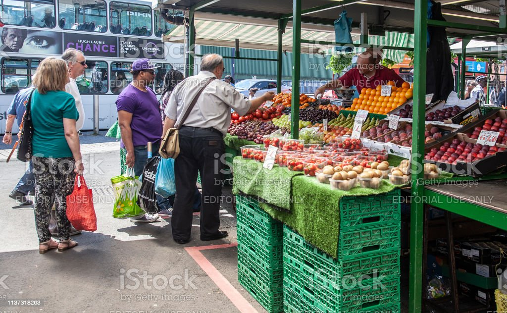 Customers And Stallholders Buying And Selling Fruit In The