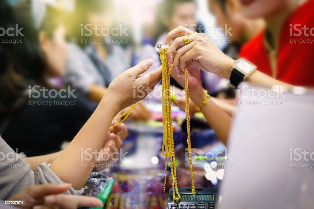 Customers are buying gold jewelry in the gold shop stock photo