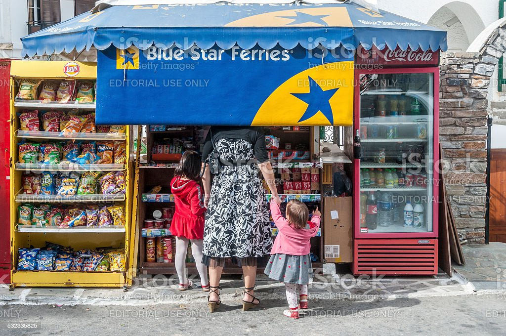 Customers at kiosk with Blue Star Ferries awning, Naxos, Greece stock photo