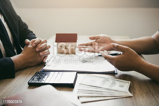 481337750istockphoto Customers buying houses are negotiating about the cost of home insurance with agents. 1170022373