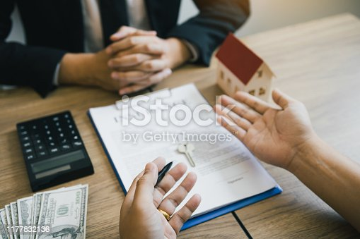 481337750istockphoto Customers buying houses are negotiating about the cost of home insurance with agents. 1177832136
