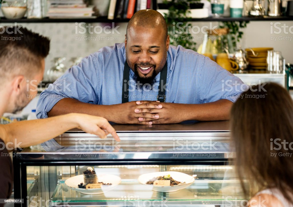 Customers choosing cake at the display fridge royalty-free stock photo