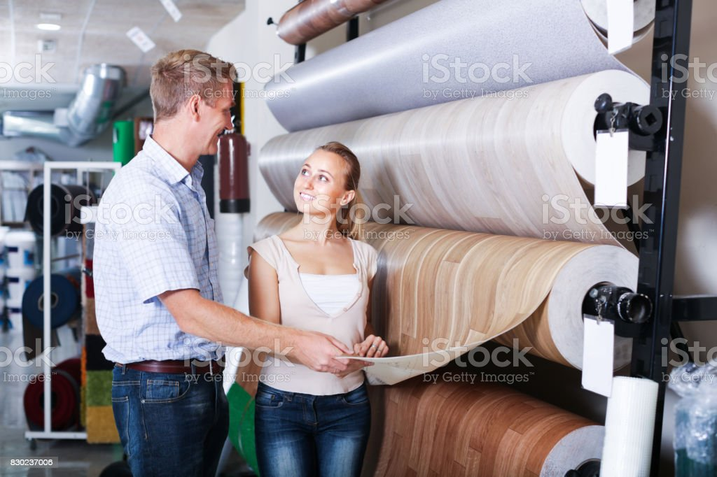 customers choosing linoleum in household section stock photo