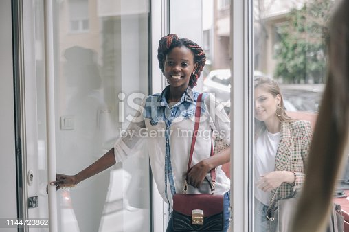 Two female friends  entering the retail store