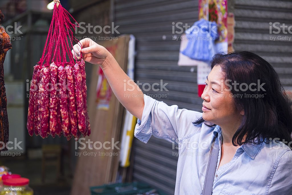 Customers examining Chinese Sausages (Waxed Meat) royalty-free stock photo