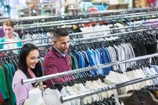 Customers in a thrift shop, rows of shirts An interracial couple shopping in a thrift shop, standing amidst long racks of clothes. discount store stock pictures, royalty-free photos & images