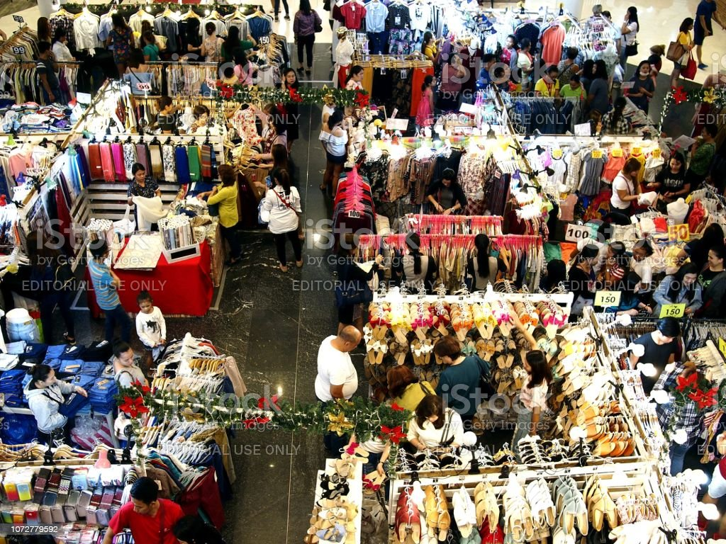 Customers of a mall bazaar choose from a variety of products from bazaar stalls. stock photo