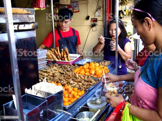 Customers of a snack food kiosk pick their choice of fried food picture id1069556906?b=1&k=6&m=1069556906&s=612x612&h=kmxhi7anns1jyy w1ps 4oif0iz456w47bswxhxkce8=
