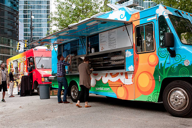 """Customers Order Meals From Colorful Atlanta Food Truck Atlanta, GA, USA - October 16, 2014:  Customers order meals from a popular food truck during their lunch hour, at """"Food Truck Thursday"""" in Atlanta. food truck stock pictures, royalty-free photos & images"""