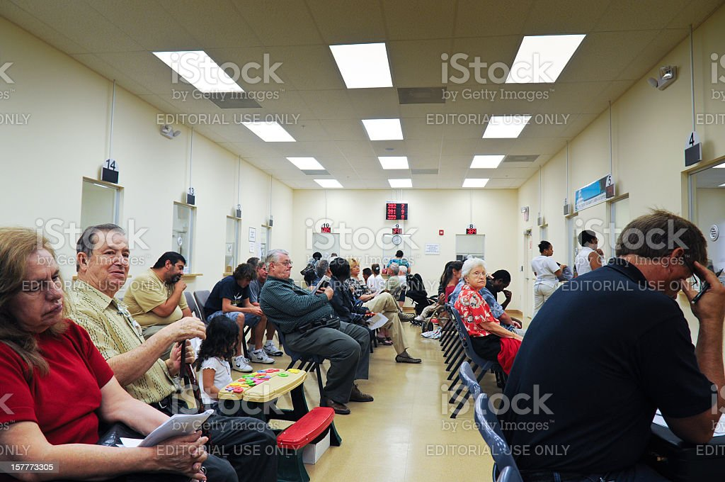 Customers que in DMV waiting room stock photo
