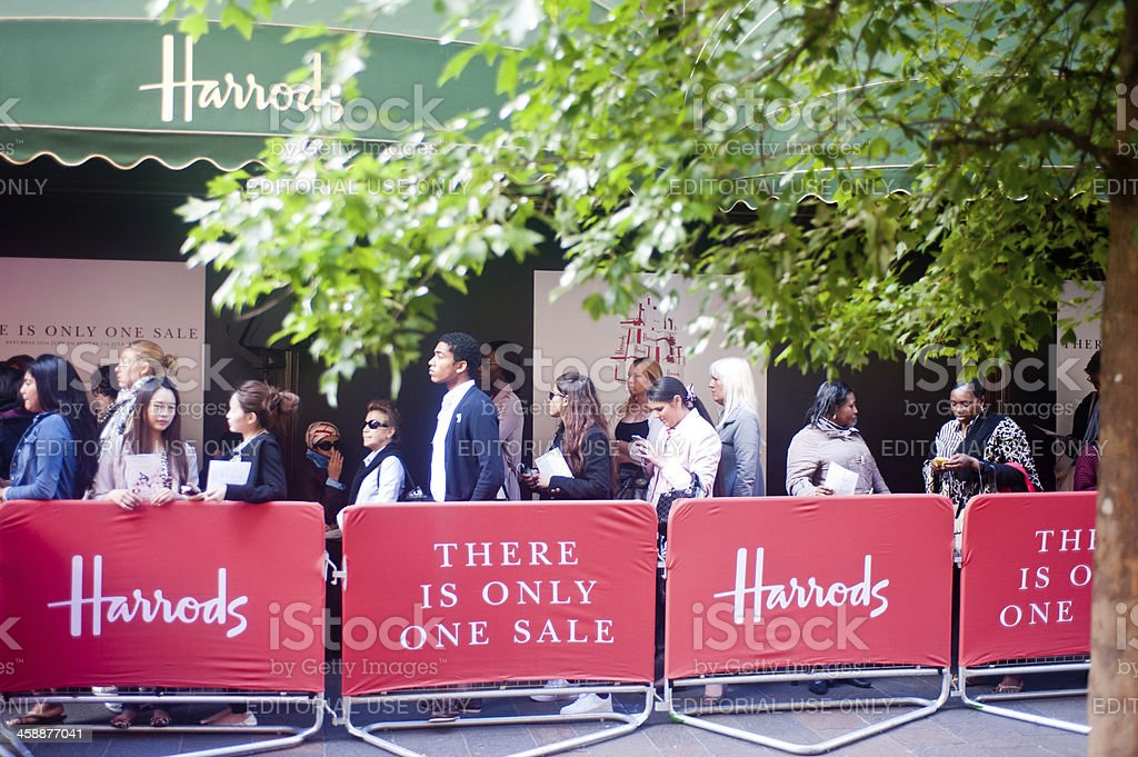 Customers queue outside Harrods in London stock photo