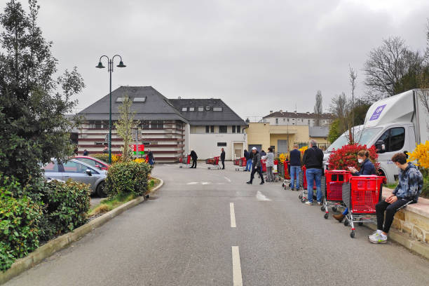 Customers queuing outside a supermarket because of the COVID-19 Lamorlaye, France - March 20 2020: Customers queuing up a meter apart to shop in a supermarket during the coronavirus crisis. central europe stock pictures, royalty-free photos & images