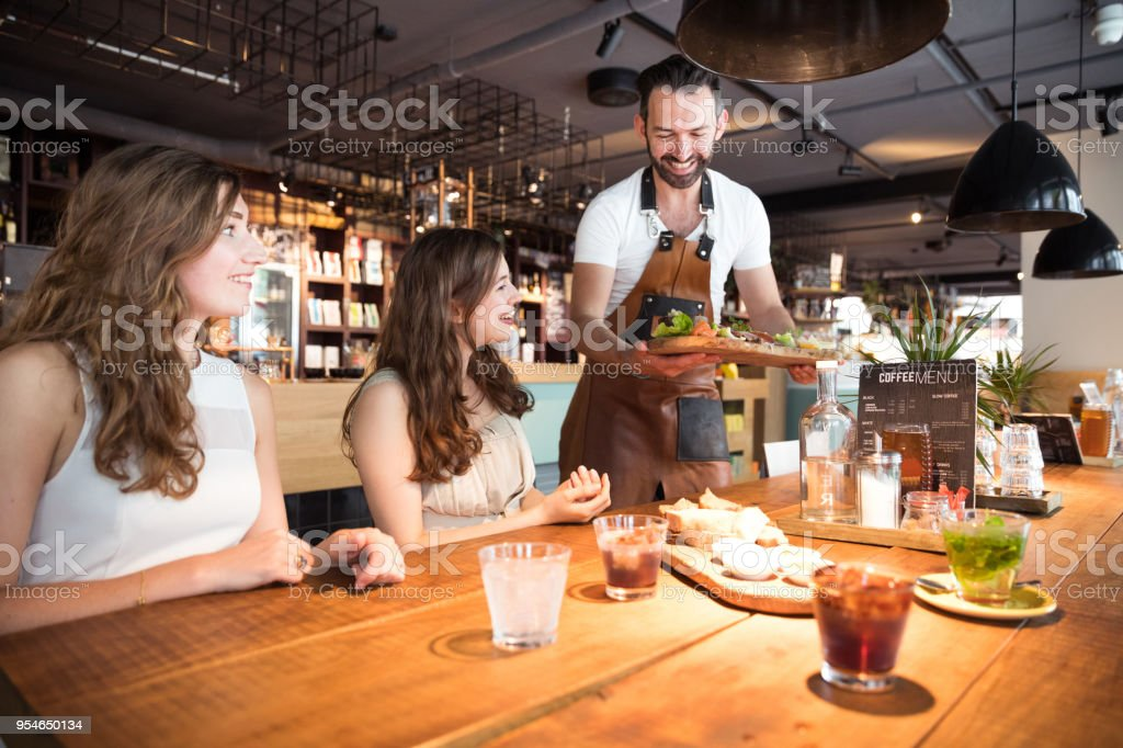 Customers served from a barista in a modern cafe stock photo