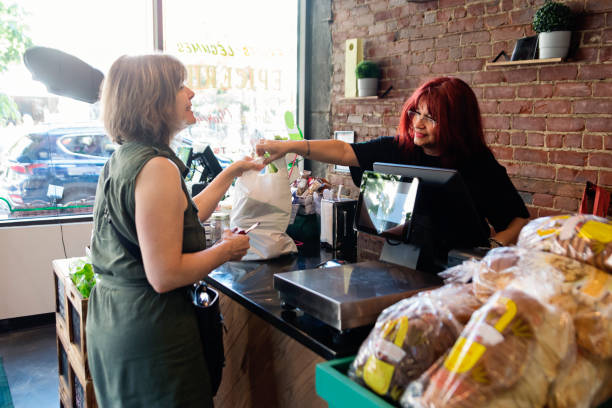 Customers shopping in small zero waste oriented fruit and grocery store. stock photo