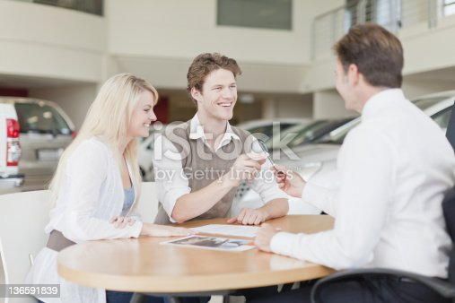 136591825istockphoto Customers signing at car dealership 136591839