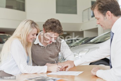 136591825istockphoto Customers signing at car dealership 136591841