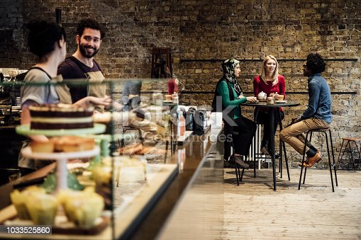 Three friends enjoying lunch in modern coffee house, two waiting staff working with cakes in cabinet
