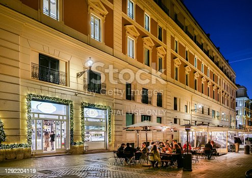Rome, Italy, December 18 -- Many customers crowd the tables of an outdoor bar in a characteristic square of the Trevi district, in the historic center of Rome, near the Trevi's Fountain. This district is much loved by the younger generations for the presence of trendy pubs, bars and restaurants, where you can find the true soul of the Eternal City. Image in high definition format.