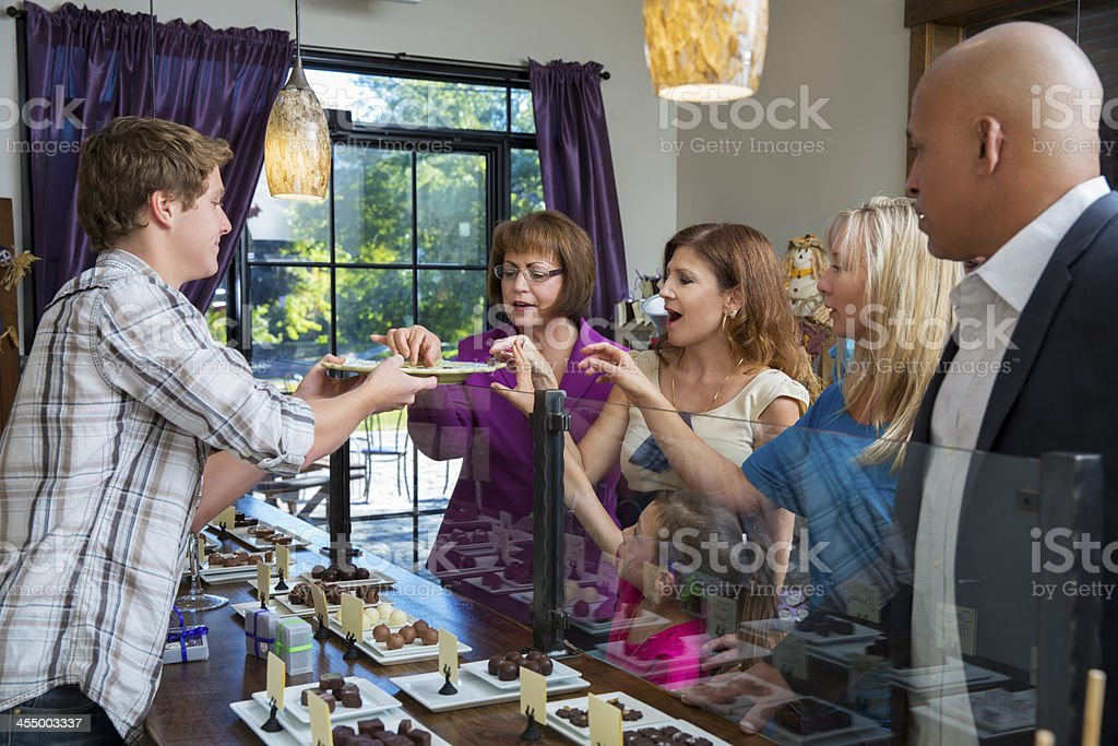 Customers tasting chocolates in candy shop stock photo