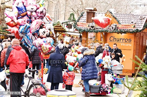 Customers, visitors and a Disney-themed balloon vendor outside a colourful Churros kiosk (fried-dough pastry) at the Christmas market (Dortmunder Weihnachtsmarkt) in Dortmund - Germany.