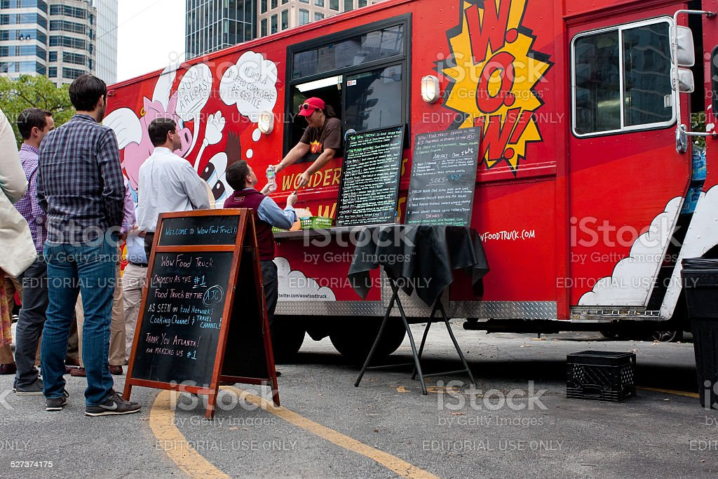 Customers Wait In Line To Order Meals From Food Truck stock photo