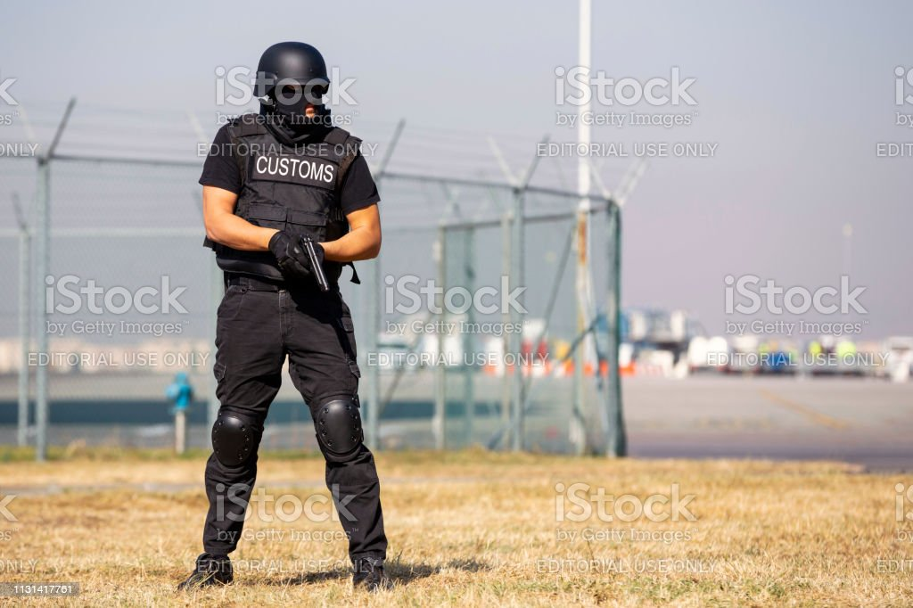 Customs and border protection officer Customs and border protection officer and Drug enforcement administration special force participates in a training at the airport for searching and seizing of illegal drugs. Unrecognizable people in black. Adult Stock Photo
