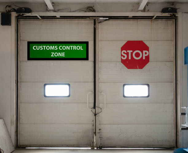 customs control zone automatic gates customs control zone automatic gates doors inside security check area with vivid red stop sign. concept of closed border for import or export customs official stock pictures, royalty-free photos & images