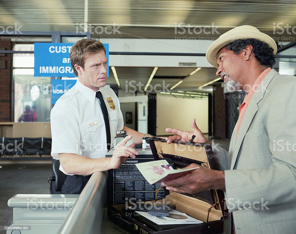 Customs officer checking man's briefcase stock photo