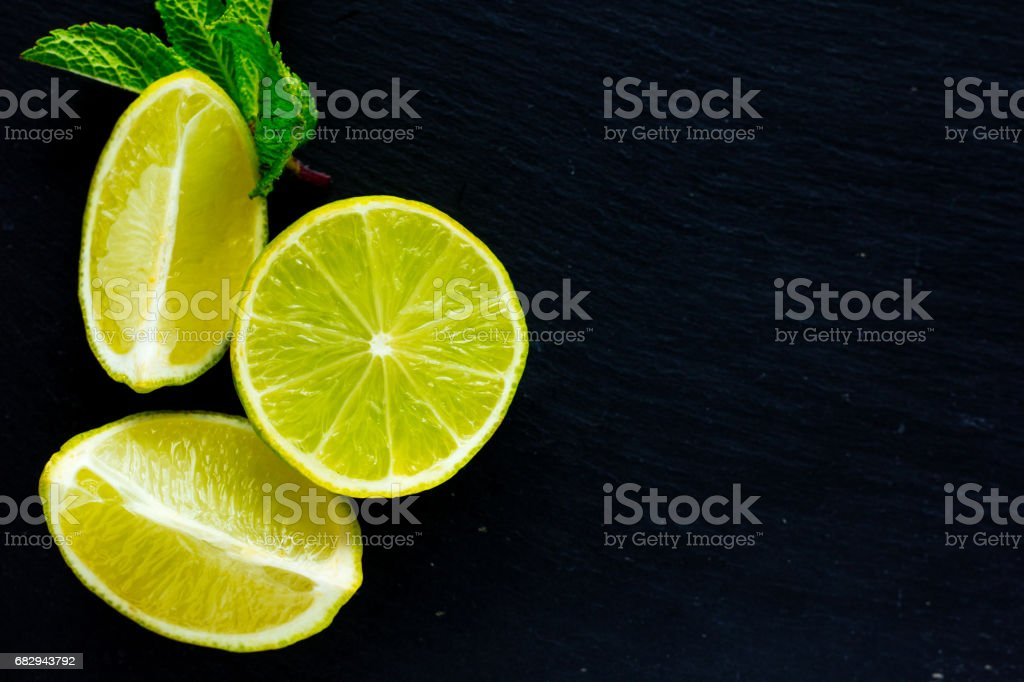 Cut and whole limes and mint leaves on black stone board royalty-free stock photo