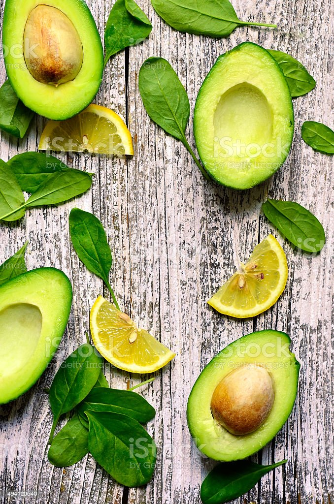 Cut avocado with baby spinach leaves and lemon slices. stock photo