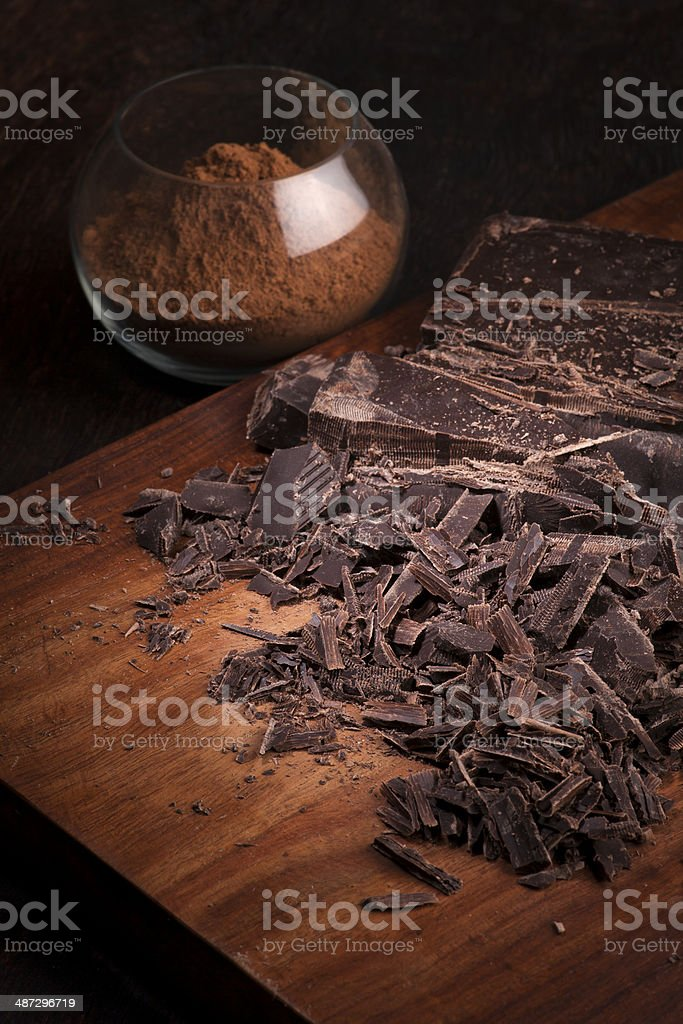 Cut Chocolate bars and cocoa powder on a wooden table stock photo