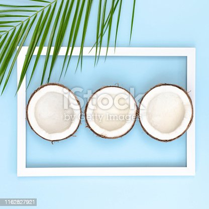 Cut coconuts on a blue background with palm branches with a frame. Summer background. Photo square format.