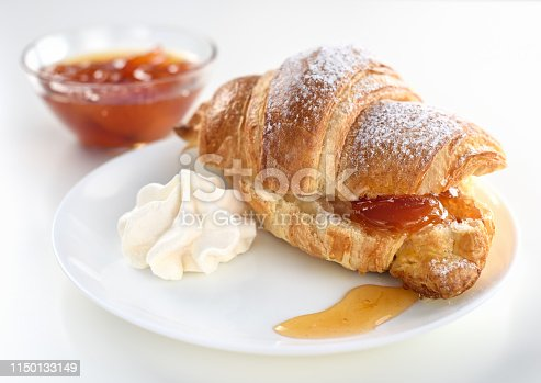 Cut croissant with apricot jam on a white plate with a whipped cream. In the back plan a bowl of apricot jam. High key.