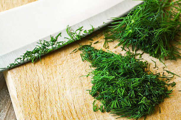 Cut Dill weed on cutting board Cut, fresh green dill weed and knife blade on cutting board. Close up, selective focus. dill stock pictures, royalty-free photos & images