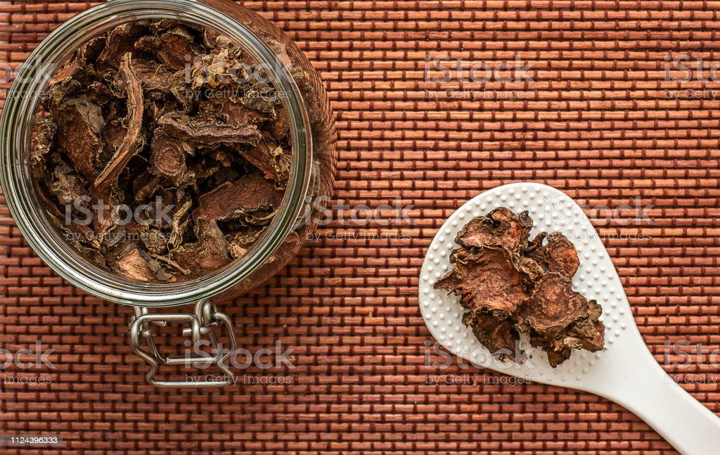 cut dry root of Rhodiola rosea in a glass jar on natural white background cut dry root of Rhodiola rosea in a glass jar on natural white background Botany Stock Photo