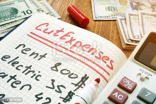 Cut Expenses for monthly home budget. Note pad and calculator.