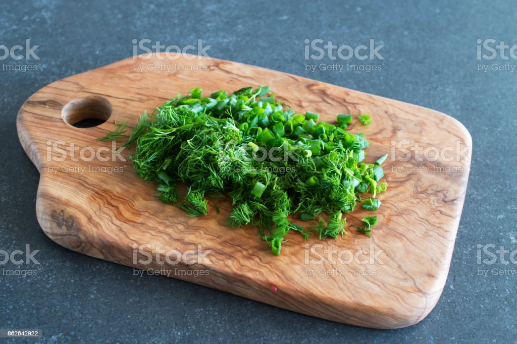 Cut fresh green onions and dill on olive wooden cvuttingboard. stock photo