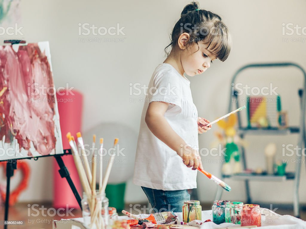 Cut girl painting in at her  home. stock photo