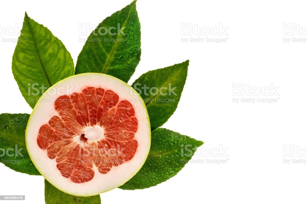 Cut grapefruit, fresh green foliage. Isolated top view. stock photo