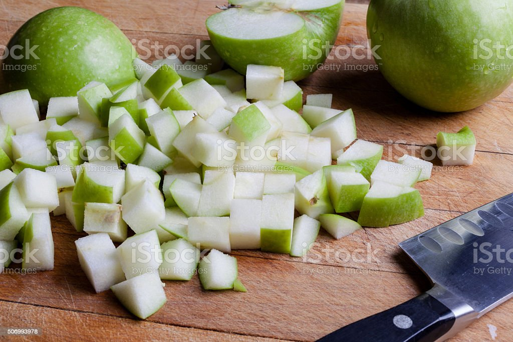 Cut green apples from side with knife stock photo