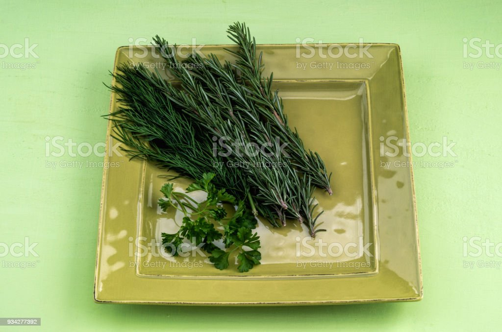 Cut herbs on a green plate stock photo
