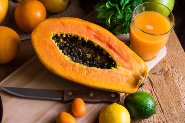 Schneiden Sie in halbe Reife Papaya, frisch gepressten Saft, Zitrusfrüchte, Orangen, Zitrone, Limette, Kumquat, frischer Minze auf Küchentisch – Foto